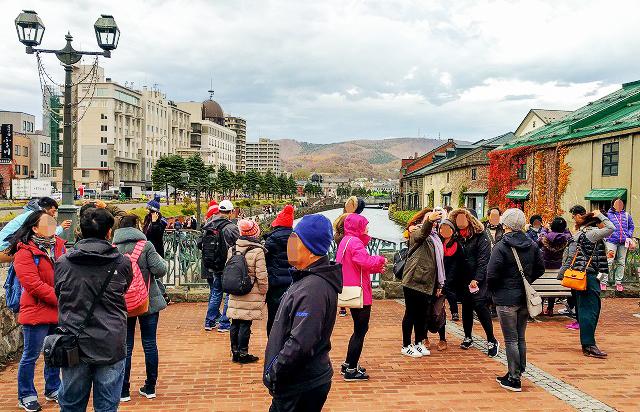 写真撮影の外国人観光客でごった返す小樽運河定番スポット