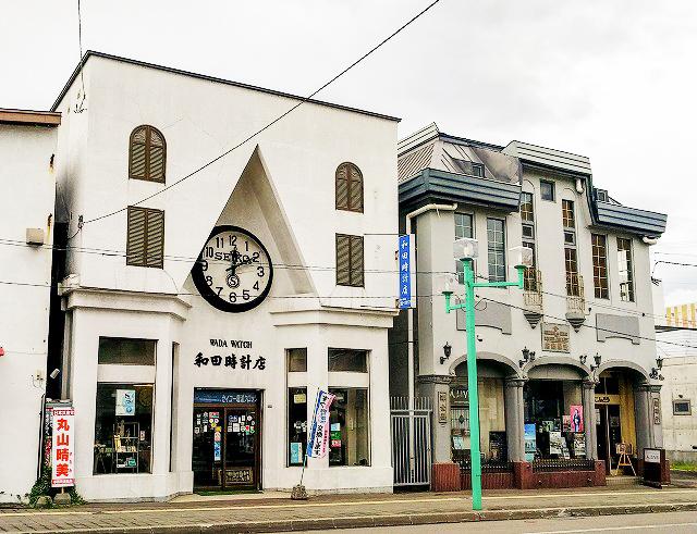 大きな時計が中心に据えられ、三角に切れ込んだデザインの和田時計店と、アムステルダムの運河脇に佇む洋館のような建築のA.LIVE