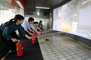 大型スクリーンに映し出された火災映像を模擬消火器で消火する消火訓練室 東京消防庁<防災館・博物館><立川防災館>から引用