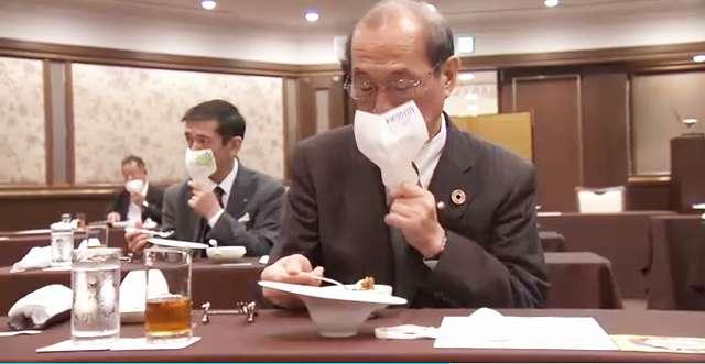 嵯峨美術大学・佐々木正子学長考案の「手で持つマスク」を使いながら食事をする男性 NHKの映像から引用